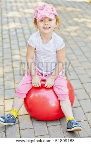 Smiling little girl sits on red ball for jumping on walkway in park