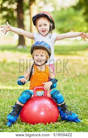 Little boy sits on red ball for jumping, girl stands behind him with her arms outstretched to sides