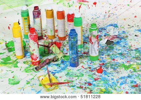 Bottle of paint and brushes on the floor with multicolored stains of paint