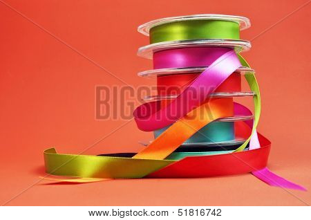 Colorful Gift Wrapping Ribbon Stack With Green, Pink, Red, Orange, Blue And Pruple Ribbons Ready For