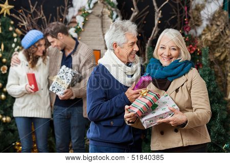 Portrait of happy senior couple holding Christmas presents with children standing in background at store