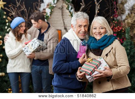 Portrait of senior couple holding Christmas presents with children standing in background at store