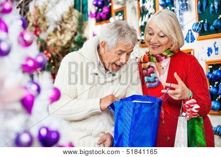 Surprised senior couple looking into shopping bag in Christmas store