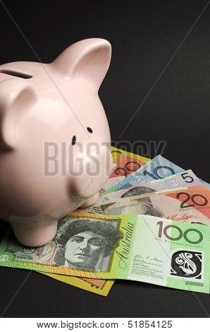 Pink Piggy Bank With Australian Money Against A Black Background, For Savings Concept. Vertical.