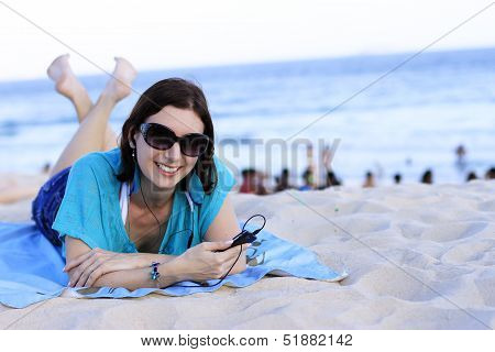 woman lying on the beach with your cell phone
