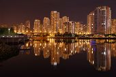 Condominiums reflect in the calm waters of False Creek at night. Vancouver, British Columbia, Canada. poster