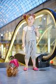 Little girl with cell phone and small dog on leash stands next to escalator in mall. poster