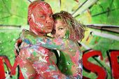 Naked girl hug bald man all in the paint in studio poster