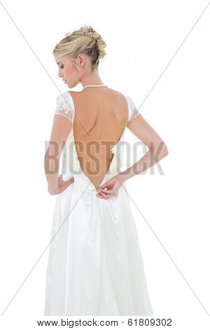 Rear view of bride getting dressed against white background