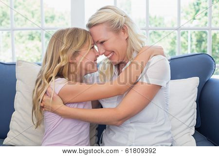 Happy mother and daughter rubbing noses while sitting on sofa at home