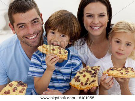 Portrait Of Family Eating Pizza In Living-room