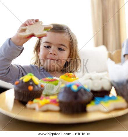 Little Girl Eating Confectionery At Home
