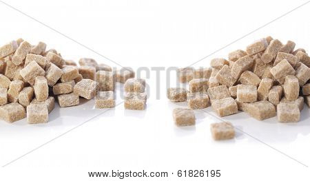 Two heaps of natural brown sugar cubes on white reflecting background