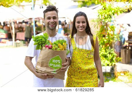 Happy couple  shopping at a open street market, carrying a shopping paper bag with a 100% organic certified label full of fruit and vegetables.