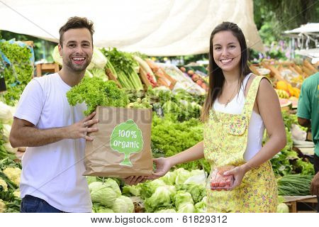 Small business owner selling organic fruits and vegetables to a woman carrying a shopping paper bag with a 100% organic certified label.