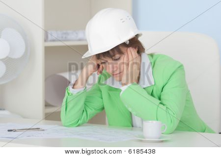 Woman - Engineer In Protective Helmet Sits At Table On Workplace