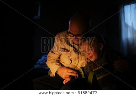 Grandfather hugs his grandson near fireplace