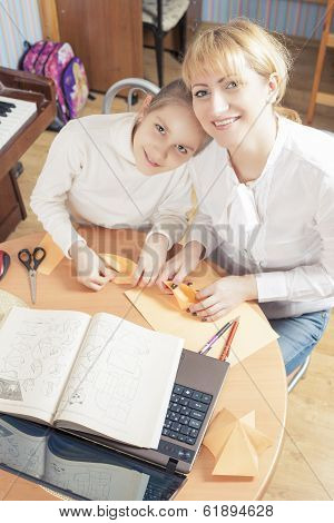 Mother With Teenage Daughter Making Origami Crafts