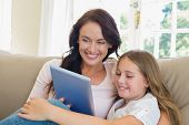 Happy mother and daughter using digital tablet in house poster