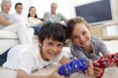 Children playing video games and family sitting on sofa poster