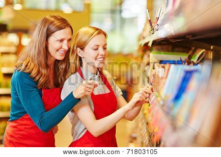 Young retal saleswoman trainee in supermarket getting help from staff