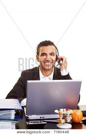 Businessman Using Headset And Laptop