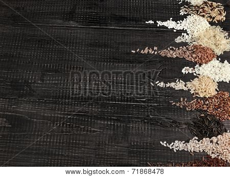 Border of colorful varieties whole grain rice in a rustic wooden surface background
