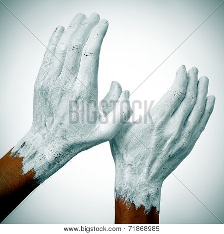 the hands of a man painted in white forming a dove of peace