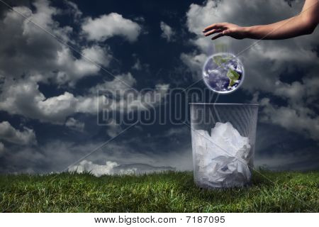 Earth being dropped in the trash