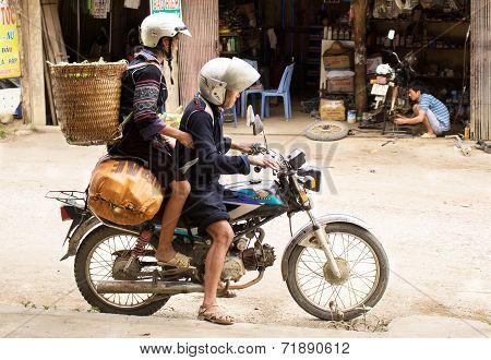 Black Hmong woman and man on motobike