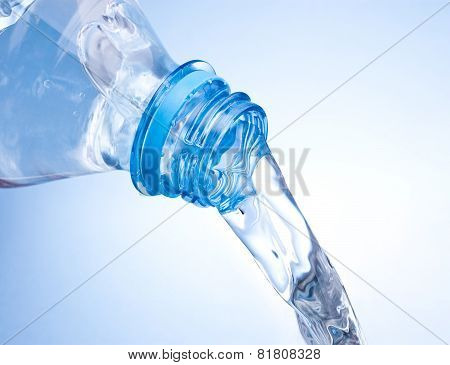 Pouring Water From Plastic Bottle On Blue Background