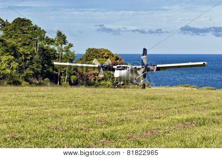 Tufi, Papua New Guinea, December 05 2008: Passenger twin engine aircraft landing on a grass airstrip