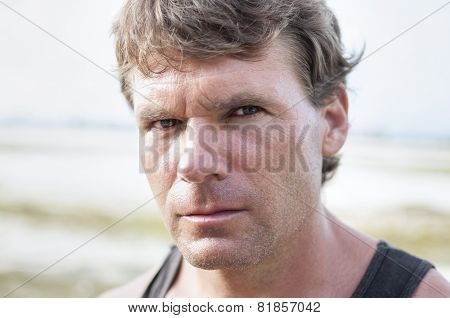 Closeup portrait of rugged Caucasian man with stern bold facial expression distinct features and intense predator eyes in undefined outdoor environment poster