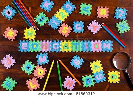 puzzle letters with pencils on wooden background