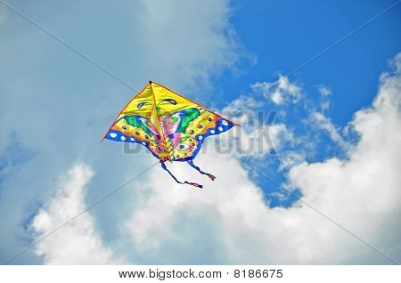 Multicolored kite with tail in blue sky