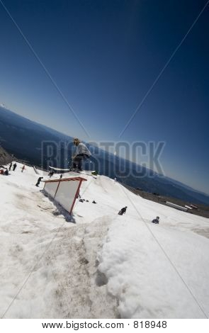 Skier jumping onto a rail