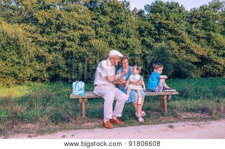 Senior man feeding to baby girl sitting in a bench