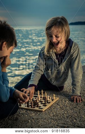 Cute children playing chess by the sea