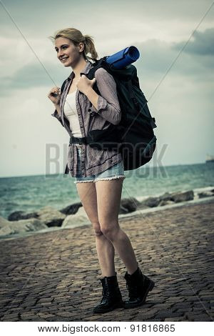 Young female backpacker by the sea