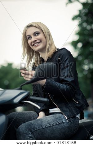 Girl sending sms message, sitting on her scooter