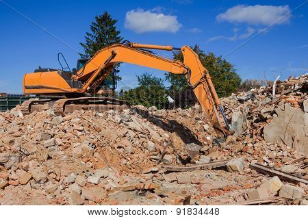 a house is demolished. excavator on the construction site. after demolition of new residential space will be created