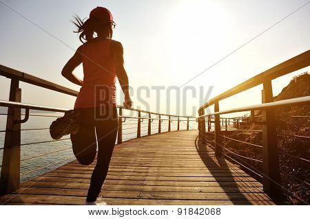 healthy lifestyle sports woman running on wooden boardwalk sunrise seaside