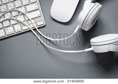 White Headphones, Keyboard And Mouse On Grey Desk