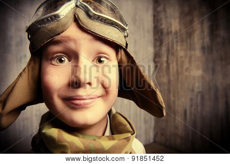 Close-up portrait of a happy kid who dreams of becoming a pilot. Childhood. Fantasy, imagination.