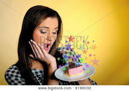 Young Beautiful Girl With Small Sweet Birthsday Cake Surprised And Emotional. Yellow Background
