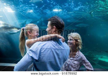 Familly enjoying behind a fish tank at the aquarium