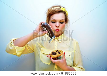 Trendy young woman is pouring chocolate sauce over chocolate chip cookie.