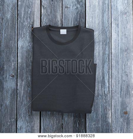 Black folded  t-shirt on wooden background