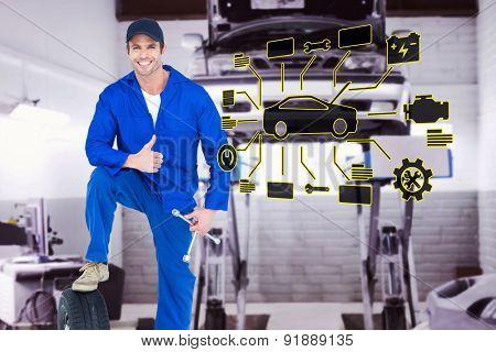 Mechanic with tire and wheel wrenches gesturing thumbs up against auto repair shop