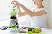healthy eating, cooking, vegetarian food, dieting and people concept - close up of young woman with blender and green vegetables making detox shake or smoothie at home poster